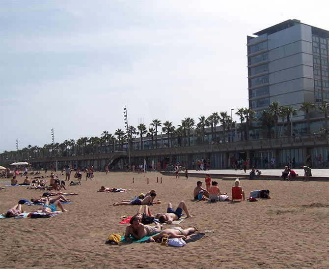 Sunbathers relax along the Barceloneta Beach in Barcelona.