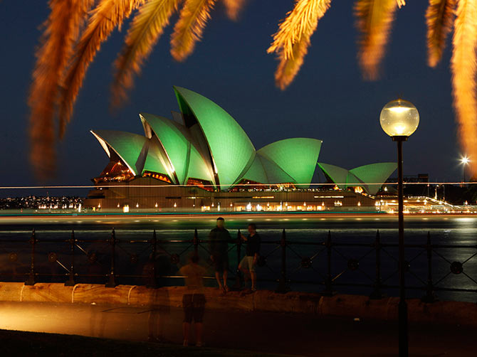 Tourists take pictures in this long exposure photograph as the Sydney Opera House is lit with green lights during St Patrick's Day celebrations in central Sydney.