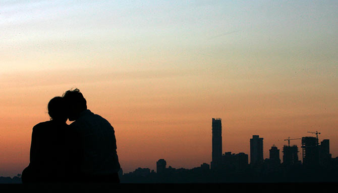 A couple look at the sunset at a seafront in Mumbai.