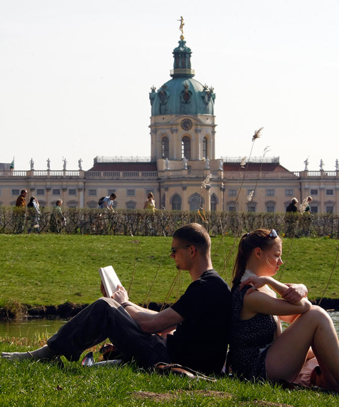 People enjoy a sunny spring day at the park of Charlottenburg castle in Berlin.