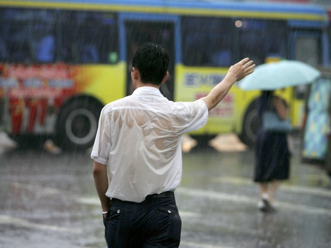 Good luck trying to get a cab! A man gestures for a taxi in the rain in Beijing.
