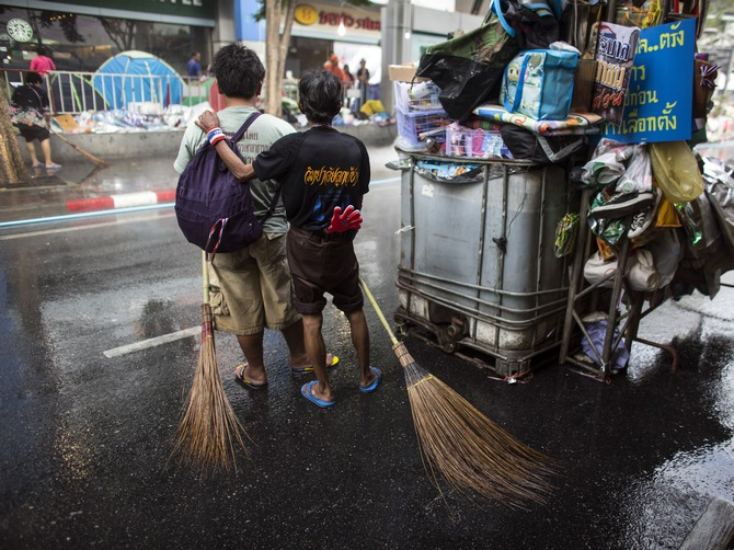 If unclean streets and coups don't bother you much, Bangkok is the place to go! :-P Anti-government protesters pause as they clean a street in Bangkok's shopping district. (Picture used here for representational purposes only.)