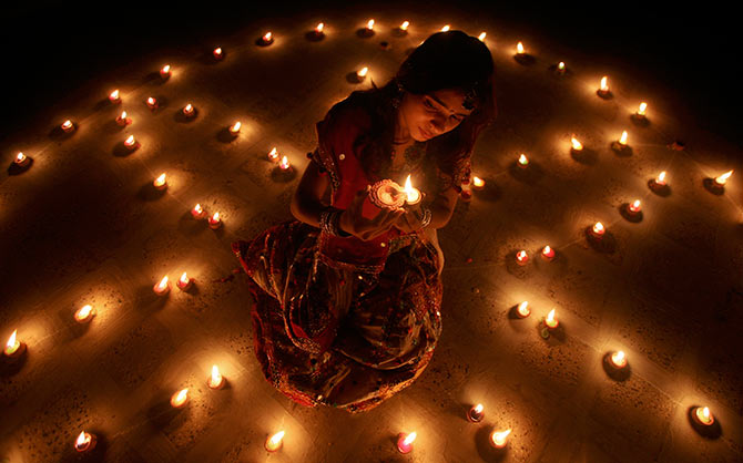 A woman lights an earthen lamp during the celebrations on the eve of Diwali.
