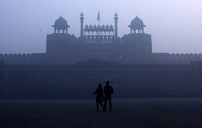 A couple walks in front of the historic Red Fort amid dense fog on a cold winter morning in the old quarters of Delhi.