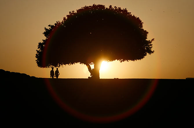 People are silhouetted against the setting sun at a park in New Delhi.
