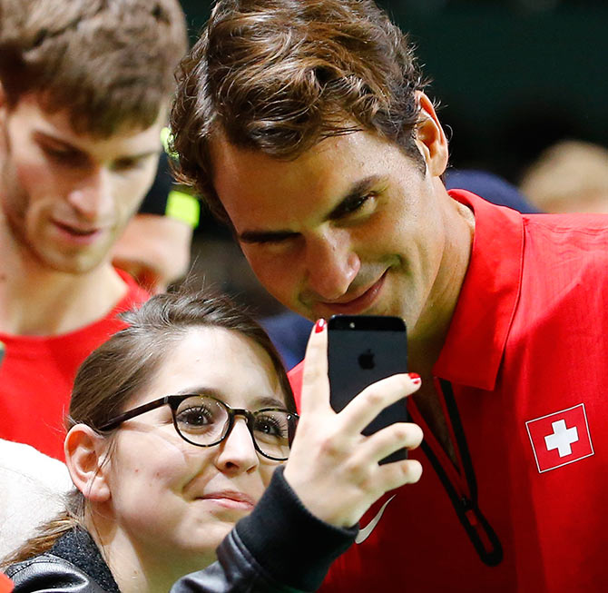 Switzerland's Roger Federer poses with a fan for a selfie after winning his Davis Cup quarter-final tennis match against Andrey Golubev of Kazakhstan in Genev