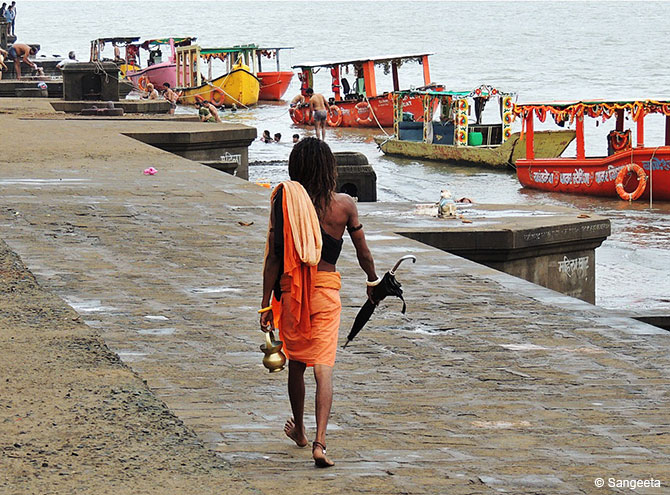 A sadhu walking in long stride on the ghats at Maheshwar