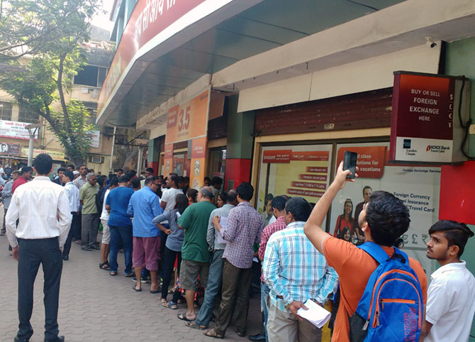 People queue up for money outside a Mumbai bank