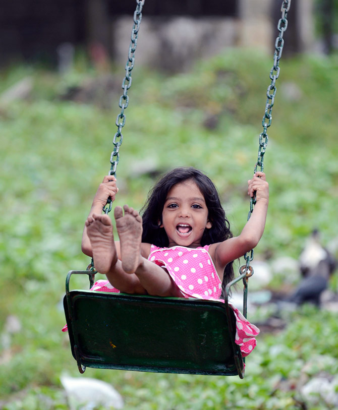 A child enjoying her ride on the swing.