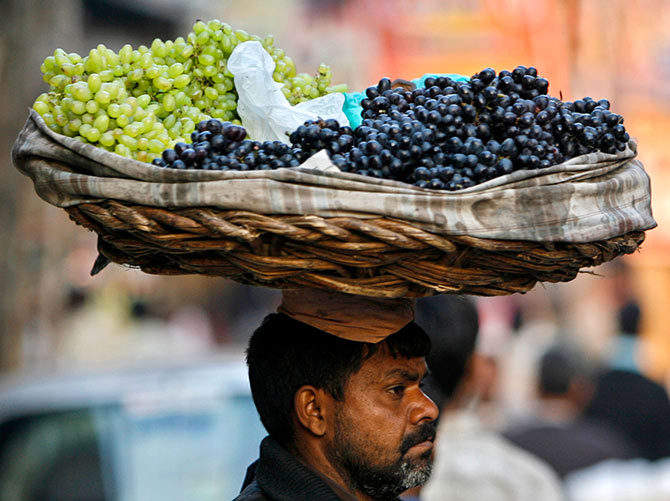 A hawker carries grapes in a basket on his head in the old quarter of Delhi, December 18, 2006. Photograph: Ahmad Masood/Reuters