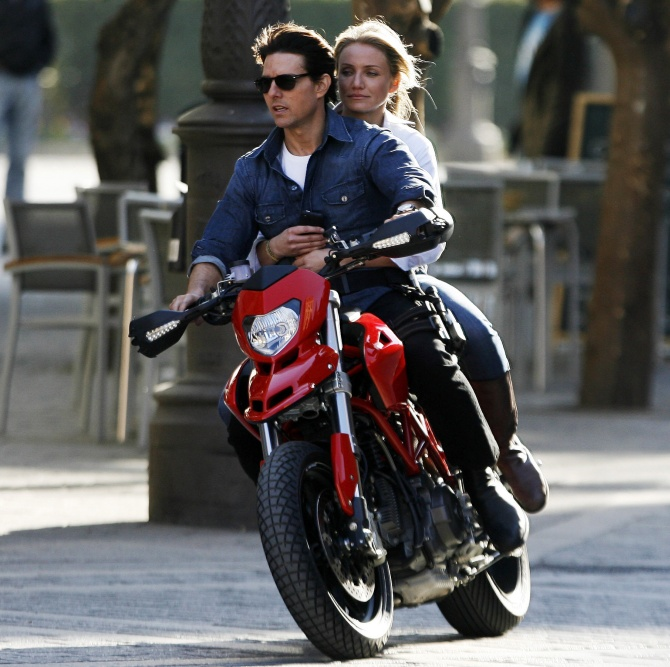 Tom Cruise and actress Cameron Diaz ride a motorbike on the set during the filming of