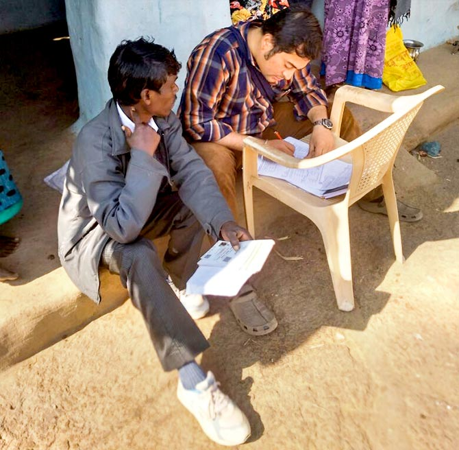 Mangesh helps a villager fill out a form