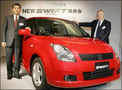 Suzuki Motor Co President Hiroshi Tsuda (L) and Chairman Osamu Suzuki introduce the new sporty hatchback Swift, equipped with a 1.3 or 1.5 liter engine at a Tokyo hotel November 1, 2004. Suzuki's global strategic car Swift will be produced in India, China, Hungary, and Japan. Photo: Yoshikazu Tsuno/AFP/Getty Images