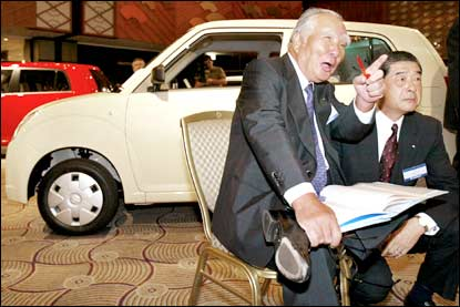 Japanese car maker Suzuki Motor Chairman Osamu Suzuki (L) and President Hiroshi Tsuda smile as they introduce the new mini-car 'Alto,' equipped with a 658cc engine, at a Tokyo hotel on Monday. Suzuki announced the company will build the new assemble plant and a new diesel engine factory in India to boost production in the country's growing market during a press conference. Photo: Yoshikazu Tsuno/AFP/Getty Images