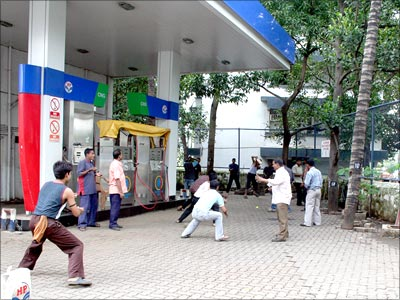 Local youth playing cricket in a petrol pump in Mumbai on Tuesday morning. The petrol dealers strike was called off on Tuesday afternoon