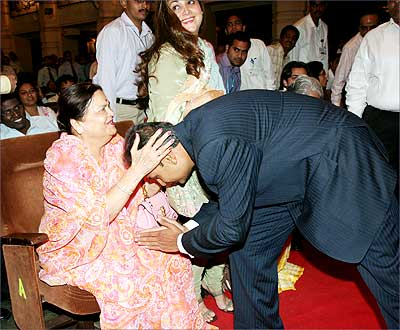 Anil Ambani seeks the blessings of his mother, Kokilaben, at the AGM of Reliance Communications Ltd in Mumbai on Tuesday. Also seen in the picture is Anil's wife Tina Ambani (center). Photograph, courtesy: Reliance Communications Ltd.