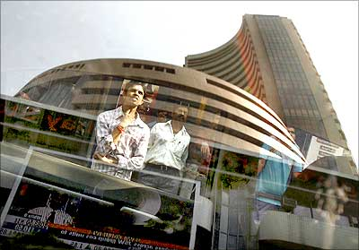 The Bombay Stock Exchange building is reflected on a glass window as people look at a large screen displaying the benchmark share index.