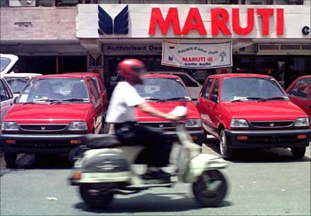 A motorcycle drives past new Maruti cars outside a New Delhi showroom.