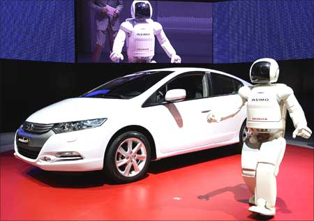 Honda's humanoid robot Asimo unveils the new Honda Insight hybrid car during the first media day of the 79th Geneva Car Show at the Palexpo in Geneva on March 3, 2009. | Photograph: Valentin Flauraud/Reuters