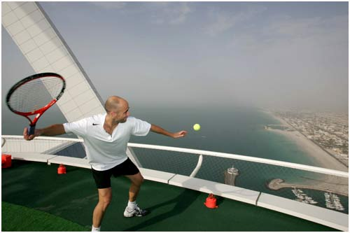 Former Tennis Ace Andre Agassi Hits A Ball Out To Sea From The Helipad Of