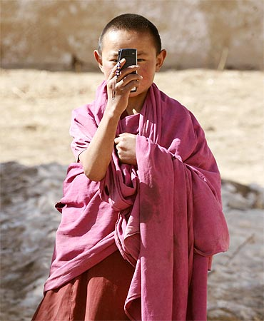 An ethnic Tibetan monk takes photographs with his mobile phone during a ceremony to celebrate Monlam, or the Great Prayer Festival, at a monastery in Aba, Sichuan province, China