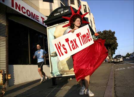 Denise Jameson wears a costume while carrying a sign to remind people passing on foot and in cars that it is income tax filing season outside a tax consulting business in San Francisco, California.
