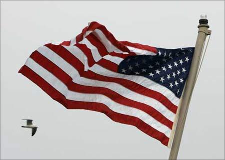 An American flag flutters in the wind as a bird flies past.   Photograph: Jo Yong-Hak/Reuters