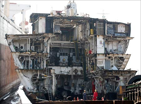 Workers dismantle a decommissioned ship at the Alang shipyard