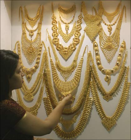 A visitor admires a gold necklace on display at the Gem & Jewellery India International Exhibition 2009 in Chennai. | Photograph:  Babu/Reuters