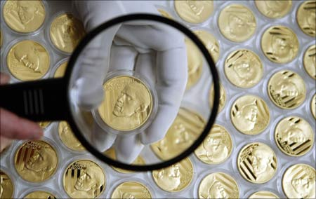 A worker checks the quality of a commemorative gold medal with the face of US President Barack Obama. | Photograph:  Petr Josek/Reuters