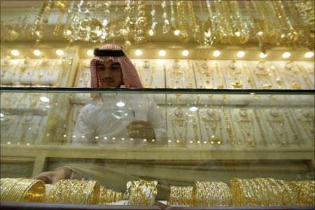 A salesman arranges gold bangles and necklaces at a jewellery shop in downtown Riyadh, Saudi Arabia. | Photograph:  Fahad Shadeed/Reuters