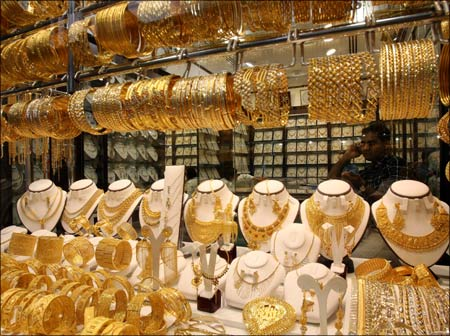 A shopkeeper sits in his shop in Dubai's gold souk. | Photograph:  Tamara Abdul Hadi/Reuters