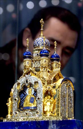 A visitor inspects a gold-and-jewel replica of a Russian Orthodox church made by Russian artists on display at a presentation for journalists in the Pushkin Museum in Moscow. | Photograph:  William Webster/Reuters