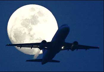 A passenger aircraft is silhouetted against the rising moon in New Delhi.