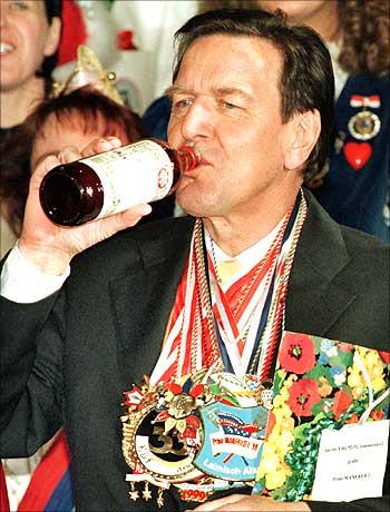Ex-German Chancellor Gerhard Schroeder tries some herbal liqueur from the Eifel region.