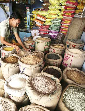 A vendor arranges sacks of cereals at his grocery shop.