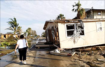 A resident walks next to a damaged house after Hurricane Ike hit the Golf of Mexico in in September, 2008.
