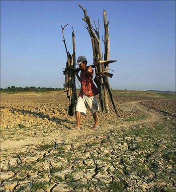 A man walks through a dried up dam after collecting firewood.