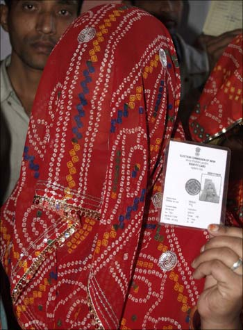 A woman shows her voter identity card as she waits for her turn to cast her ballot at a polling station in Bikaner.