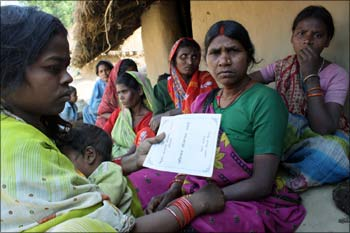 A labourer displays her job card, given under the NREGA, plan at Korhar village near Patna.