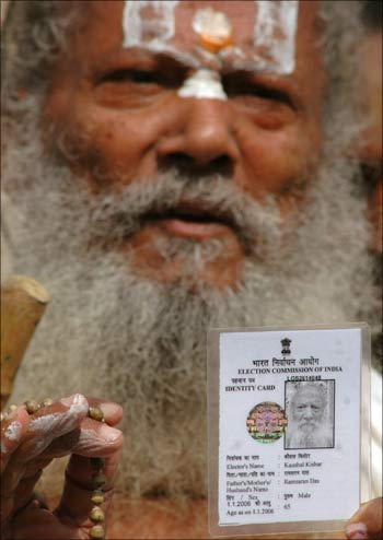A voter displays his identity card.