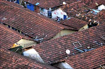 Slum dwellers chat amid cluster of houses in Kolkata.
