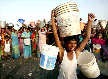 Slum dwellers shout slogans as they carry empty containers during a protest in Chandigarh.