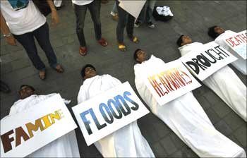 Volunteers pose as dead bodies during an event to create awareness on climate change in Mumbai.
