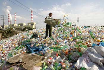 A worker dumps plastic bottles at a recycling centre in Ningbo, Zhejiang province, China.