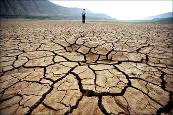 A Chinese man walks on a dried-up riverbed at Huangyangchuan reservoir in Lanzhou.