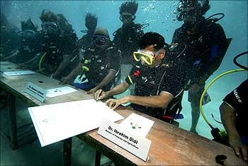 Maldivian Minister of Fisheries and Agriculture Ibrahim Didi signs a declaration calling on countries to cut down carbon dioxide emissions ahead of a major UN climate change conference.