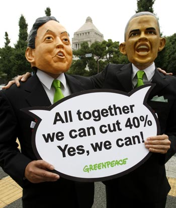 Greenpeace activists wearing masks depicting Japan's Prime Minister Hatoyama and US President Obama.