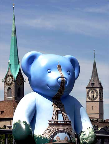 A teddy bear with a painted Eiffel tower on its chest stands in front of the Fraumuenster church (L) and the St. Peter church on the Quai bridge in Zurich.
