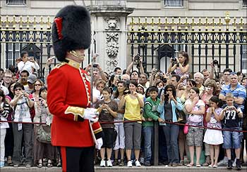 Tourists take pictures of the Changing of the Guard Ceremony at Buckingham Palace in central London.